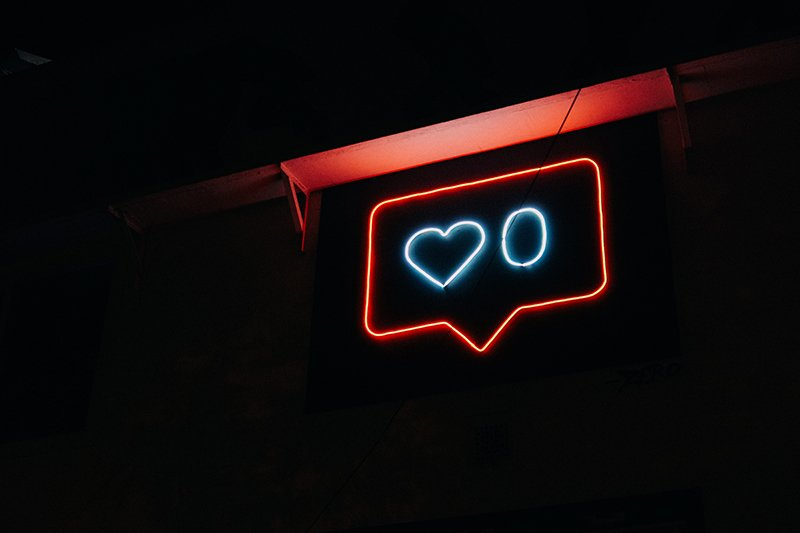 A neon sign with a blue heart and a 0 for 0 likes