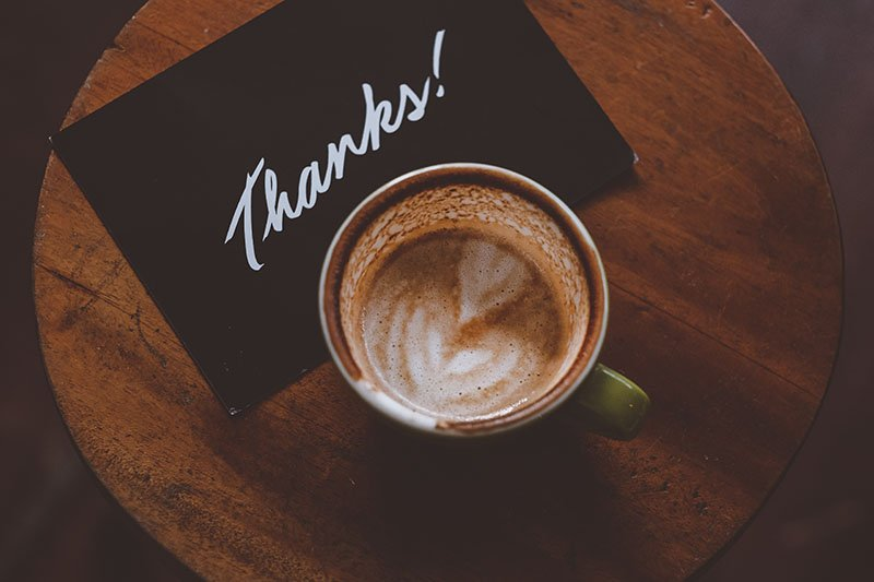 A coffee cup on a table with a card that says thanks. Showing proper appreciation will help you get more engagement with customers.