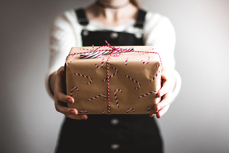 A woman holding a wrapped gift. Giving an appropriate gift can be a great way to show customer appreciation.