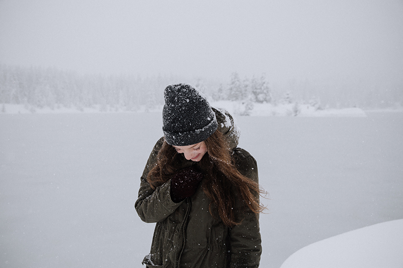 A woman wears a black hat, coat, and mittens outside while it snows.