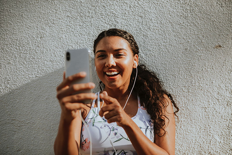 A woman with curly brown hair taking a video of herself on her phone while wearing headphones. Including videos can help you write approachable messages.