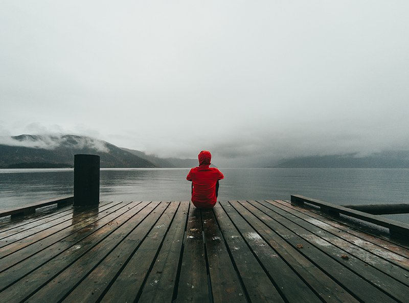 A person in a red jacket sitting on a dock facing away. You can't build a relationship through text if you don't respect boundaries.