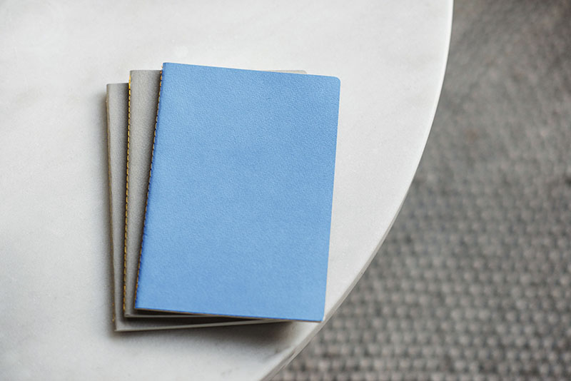 Three notebooks on a table with a blue notebook on top.