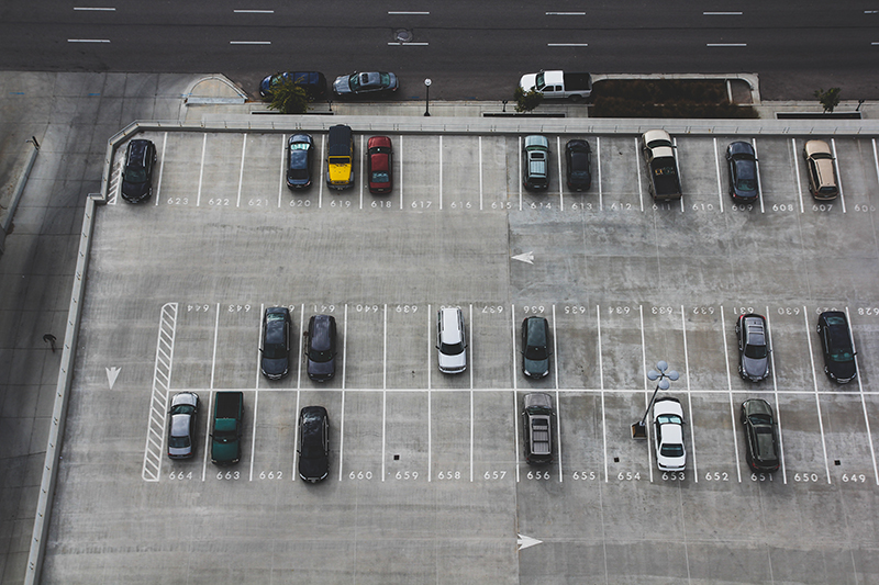 Aerial view of cars in a parking lot with numbered stalls.