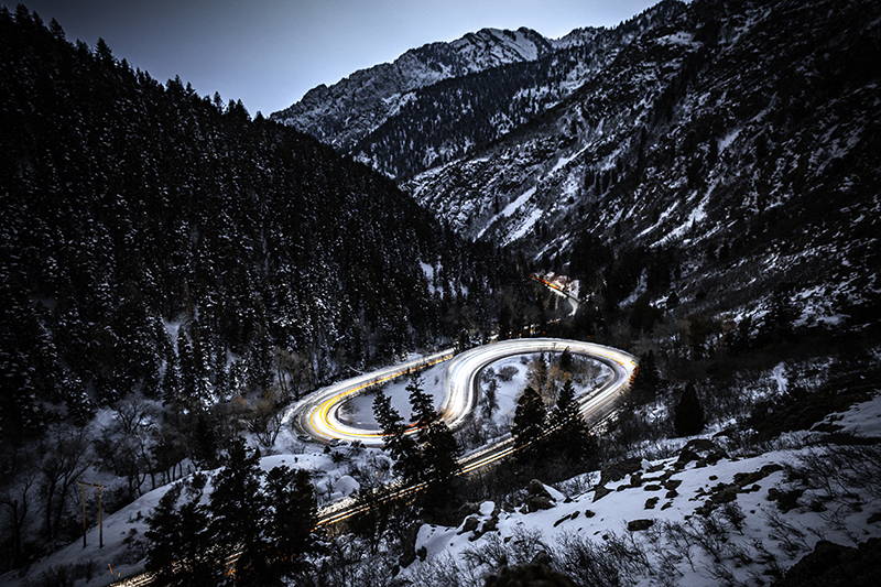 View of an s curve road surrounded by snowy mountains with lights from cars going by