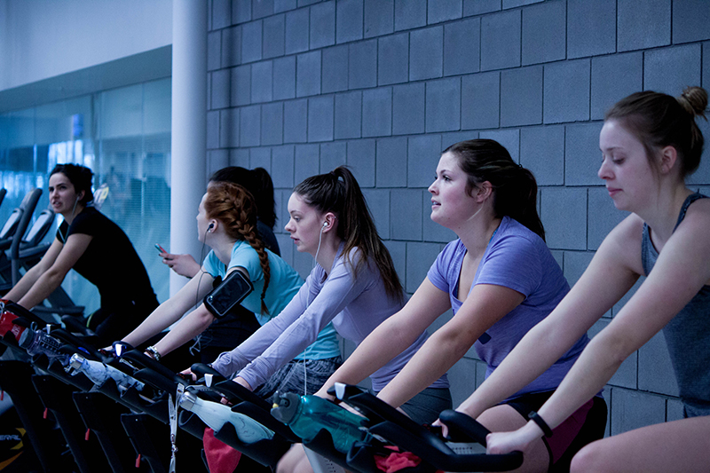Women in a line on stationary bikes at a gym.