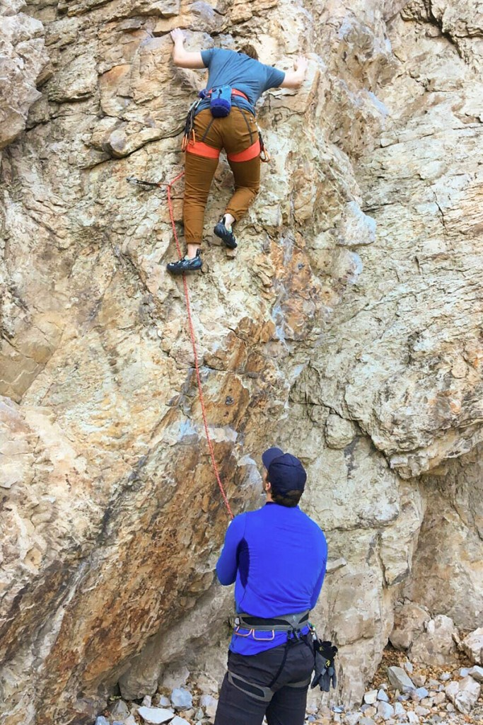 A woman lead climbing while a man belays. A key component of lead climbing is follow-up communication.