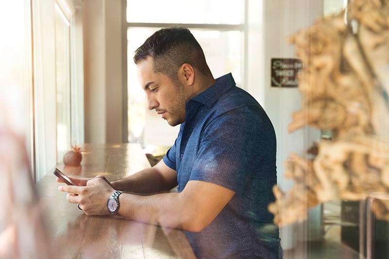 Man sitting at a counter texting.