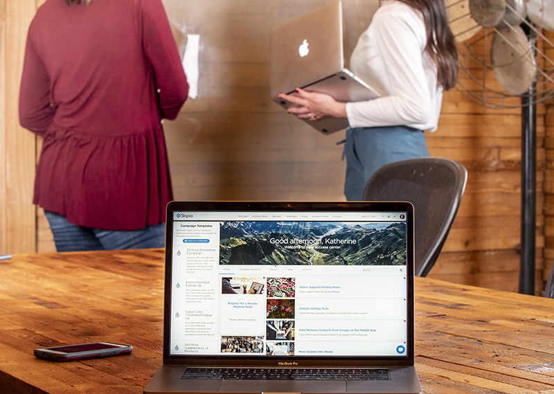 Laptop on a wooden table with the Skipio Success Center open. The features Skipio provides make it more than a business texting platform.