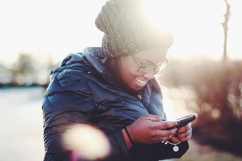 A woman wearing a beanie and a puffy coat looking at her phone and smiling.