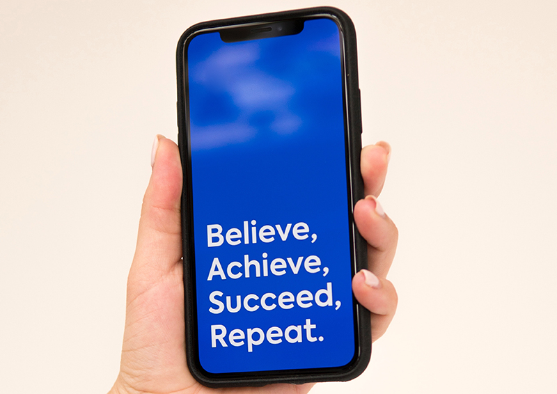 A photo of a phone with a blue design that says believe, achieve, succeed, repeat.