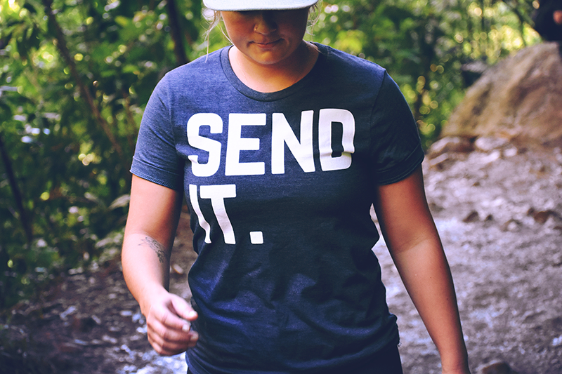 A woman hiking wearing a t-shirt that says send it.