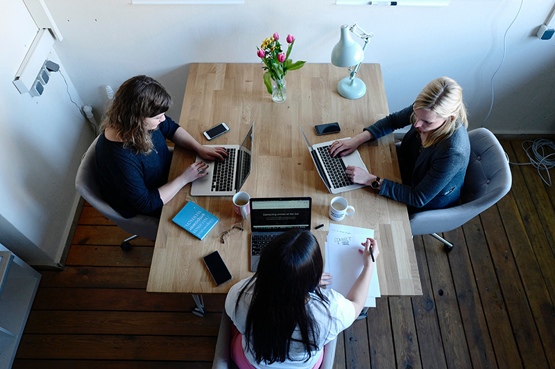 3 women on laptops having a meeting at a wooden table.
