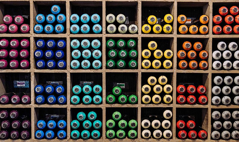 Colorful cans of spray paint organized by color in cubbies.