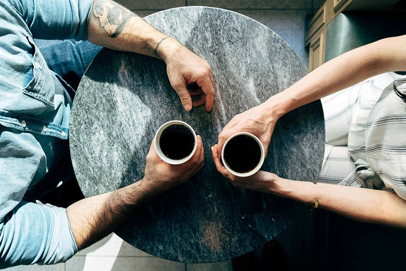 People sitting at a table with mugs between them