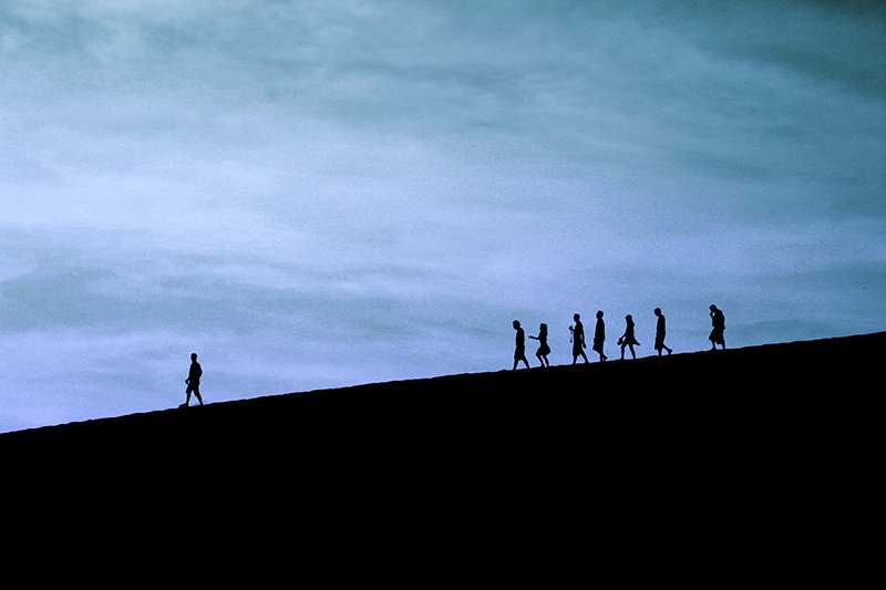 Silhouette of group of people walking on a hill at dusk with one person walking further ahead.