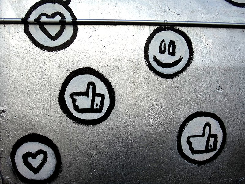 Hearts, thumbs up, and smiley face painted on a silver wall.