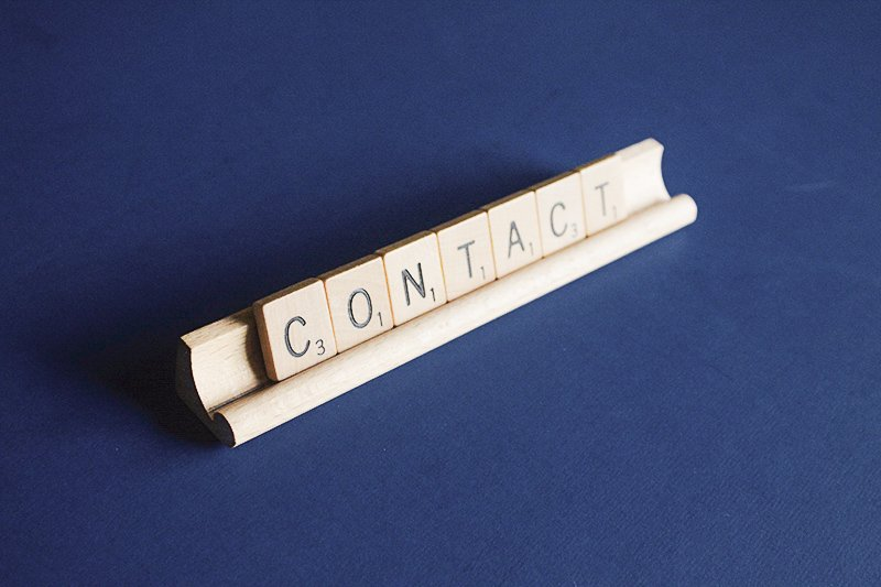 Scrabble letters on a tray that spell out the word contact.