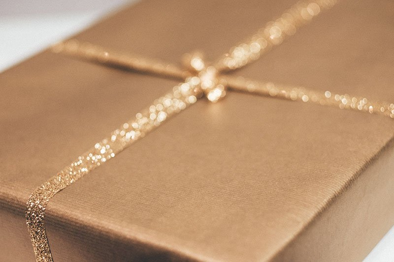 A thin gold box with a gold ribbon. Showing appreciation for customers can be part of workplace gratitude.