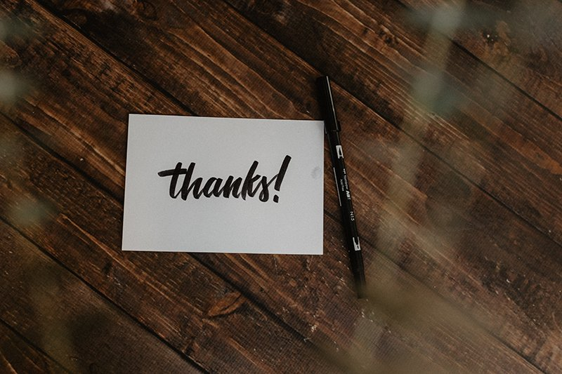 A card with thanks written on it in a script font. Cards could be a part of showing more workplace gratitude.