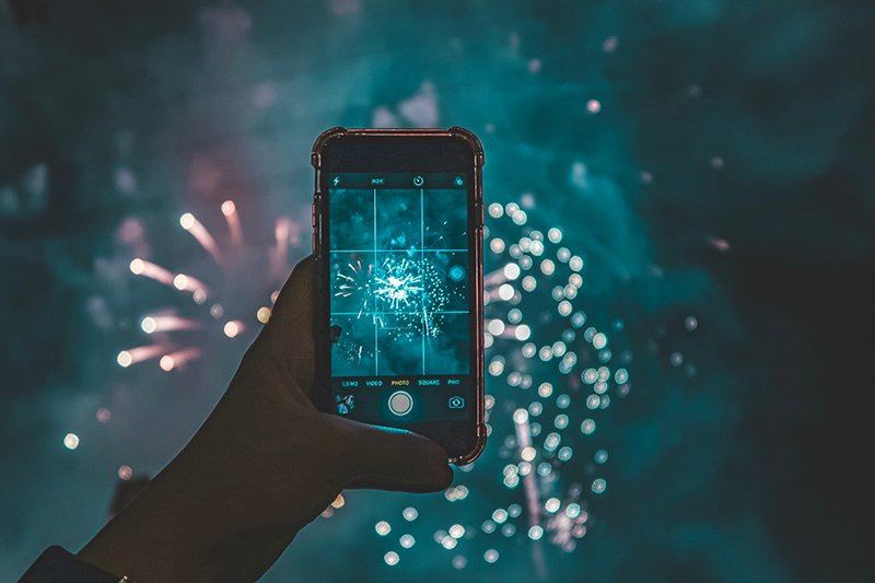 A person holding up their phone to take a picture of fireworks.
