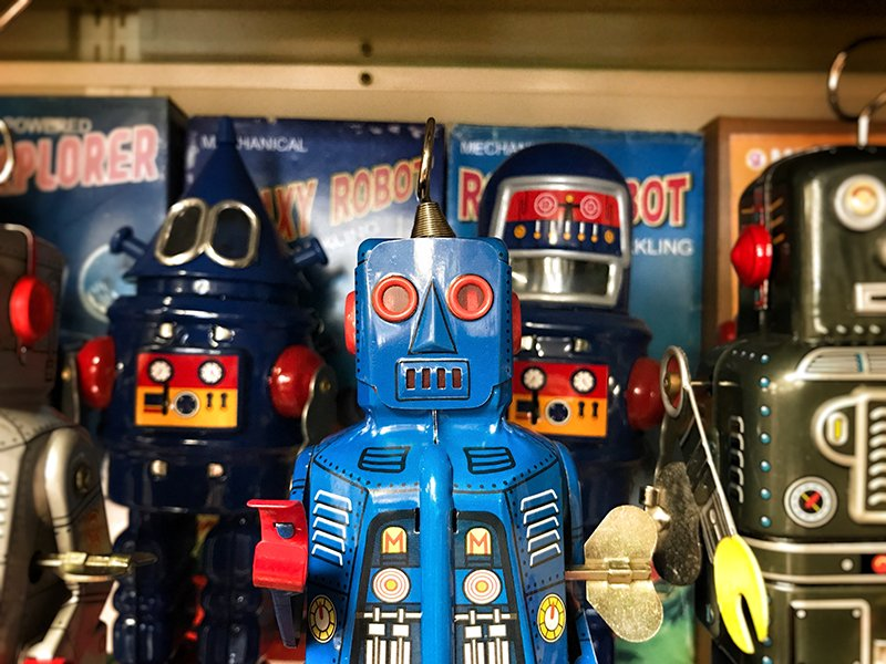 Different colored robot toys standing up on a shelf.
