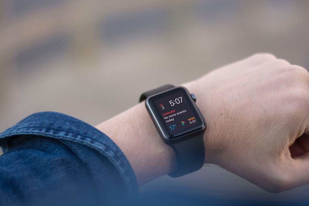 A person wearing a black Apple watch